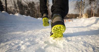Człowiek w butach do biegania z żółtym bieżnikiem – dostosowanych do warunków zimowych